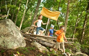 Kids playing with tree ship in forest